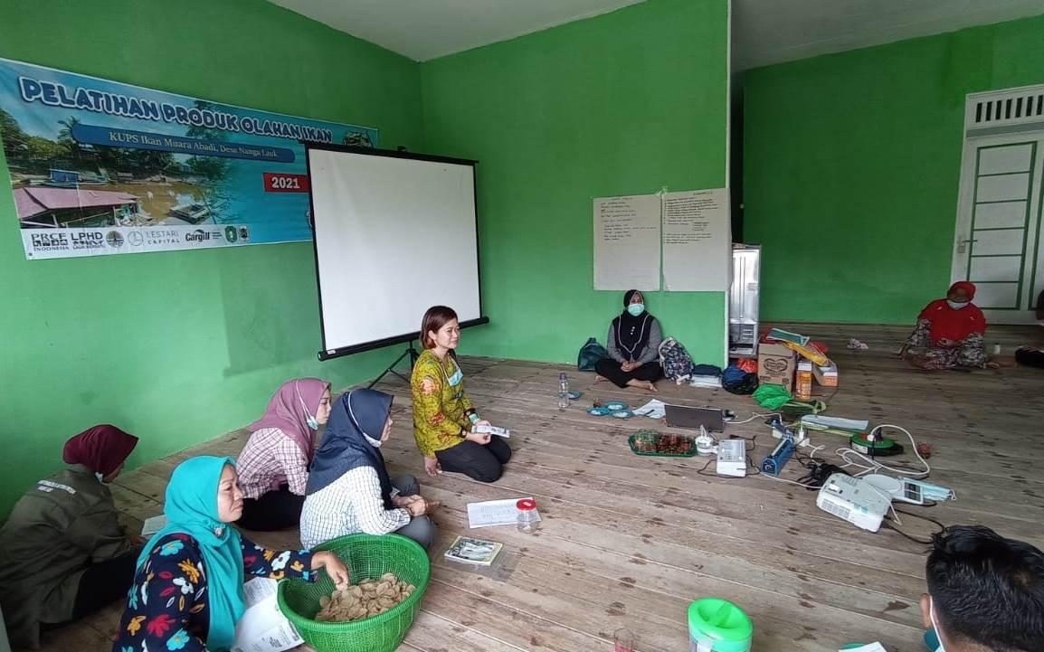 Aries Nursejari dari Dinas Perikanan Kapuas Hulu sedang melatih pembuatan kerupuk kering