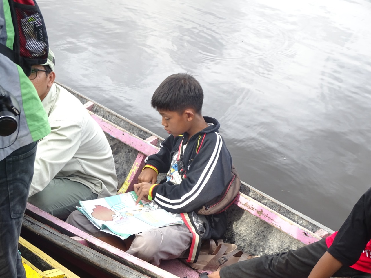 Seorang pelajar sedang membaca di atas perahu baca